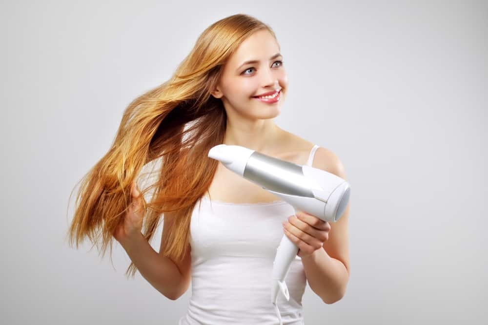 Mädchen föhnt sich die Haare