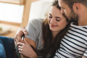 Man hält junge Frau im Arm